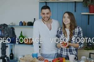 Cheerful attractive couple recording video food blog about cooking on dslr camera in the kitchen at home
