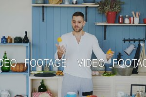 Funny cheerful man juggle with orange mandarins it the kitchen at home