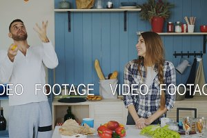 Attractive loving couple having fun in the kitchen. Handsome man juggle with fruits to impress his girlfriend