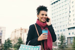 Attractive mixed race business woman talking smartphone and drinking coffee walks in city street with shopping bags