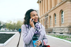 Attractive mixed race girl talking smartphone and drinking coffee walks in city street with bags. Young woman walking after shopping on mall sale
