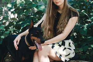 Young girl with dog Doberman