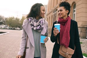 Two beautiful mixed race woman friends drink coffee and talks after shopping and walking city street