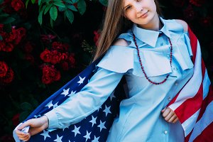 The young beautiful girl stands against the roses with the flag of the United States of America
