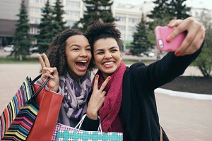 Two cute african american woman taking selfie with shopping bags and smiling. Friends have fun after visiting mall sale.