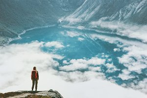 Travel woman above clouds and lake