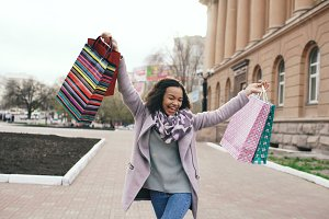 Attractive mixed race girl dancing and have fun while walking down the street with bags. Happy young woman walking after shopping on mall sale