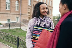 Two young african american women sharing their new purchases in shoppping bags with each other. Attractive girls talking and smiling after visiting mall sales