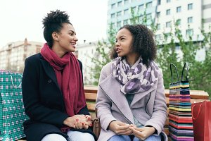 Two young african american women sharing their new purchases in shoppping bags with each other. Attractive girls talking while sitting on steet bench