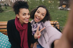 Two cute african american woman taking selfie on smartphone with shopping bags and smiling. Girlfriends sitting on street bench have fun after visiting mall sales