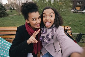 Two cute african american woman taking selfie on smartphone with shopping bags and smiling. Girlfrie