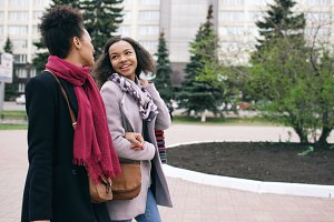 Two attractive mixed race women with shopping bags talking and walking down the street. Girlfriends have fun after visiting mall sale