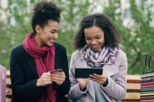 Two attractive mixed race women with paper bags sitting on bench and using tablet computer and credit card for online shopping