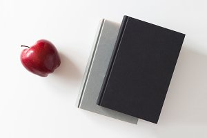 Red apple and books on white table