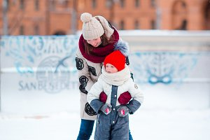 Little adorable girl with her mom skating on ice-rink