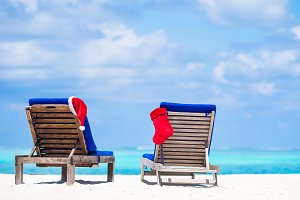 Red Christmas stocking and Santa Hat on beach beds