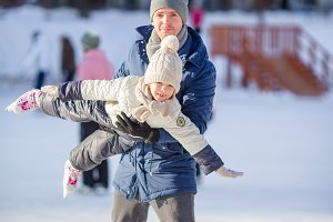 Family of father and kid having fun on skating rink outdoors
