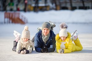 Family enjoy wintersport on ice-rink outdoors