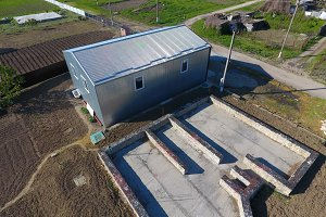 Buildings on the site. Hangar from metal profile, corrugated. The foundation of the house.