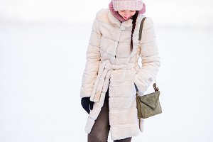 Happy young woman on ice rink outdoors
