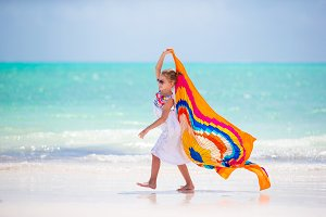 Little girl hve fun on the beach. Kid enjoy beach vacation with pareo