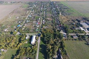 Top view of the village. One can see the roofs of the houses and gardens. Road in the village. Village bird's-eye view