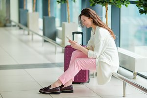 Young woman in international airport with her luggage and smartphone waiting for her flight