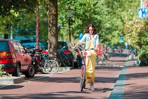 Happy young woman on bike in Amsterdam