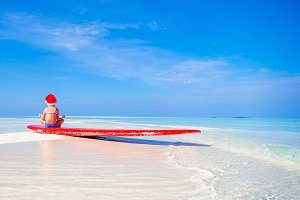 Little girl in Santa hat on white beach during Chrismas vacation