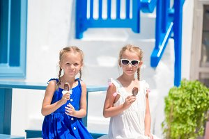Two girls in blue dresses sitting on blue chairs and table on street of typical greek traditional village with white houses on Mykonos Island, Greece, Europe.