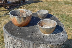 Three wooden bowl on a stump