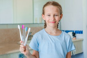Little beautiful girl with white teeth with toothbrushes in hands in the bathroom