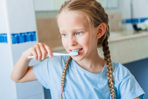 Little adorable girl brushes teeth in the bathroom