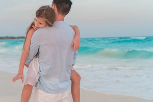Adorable girl and young father at tropical beach. Family in the evening on the beach