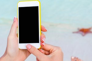 Closeup smartphone in female hands on the background of turquoise ocean at tropical beach
