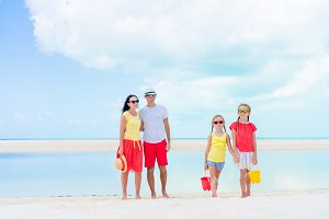 Family of four on beach vacation having a lot of fun
