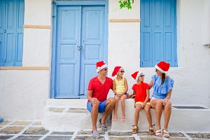 Family on Xmas vacation. Parents and kids at narrow street in traditional greek village celebrating Christmas and New Year