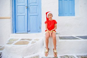 Little girl in santa hat outdoors in the city on Christmas vacation