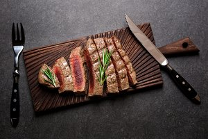 steak on cutting board with rosemary