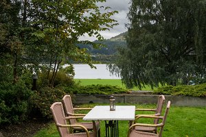Table and chairs on lawn by lake on cold autumn day
