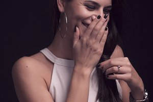 one young beautiful woman portrait, sincere candid giggling, covering her mouth with hand. black background, white dress, studio. upper body shot.