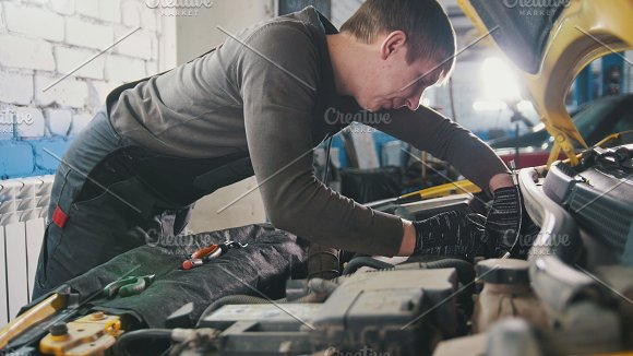 Mechanic in car repairing service - diagnostics in engine compartment