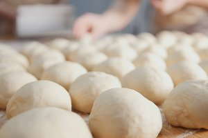 Cook is shaping meat pies by hands in the bakery