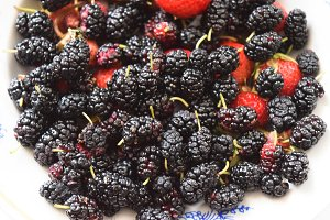 Mulberry with strawberries on a plate. Macro fruit