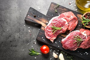 Raw beef steak with herbs.