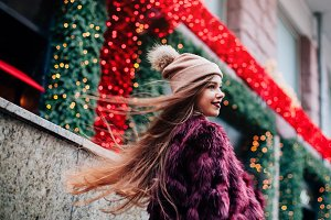 Close up fashion street stile portrait of pretty girl in fall casual outfit Beautiful brunette posing outdoor Dynamically young girl walks down the street.Hair fluttering in the wind.