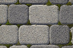 Industrial building background of paving slabs with overgrown with moss in the cracks. Texturing background