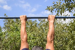Hands on the bar close-up. The man pulls himself up on the bar. Playing sports in the fresh air. Horizontal bar.