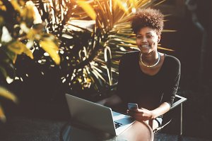 Cheerful black girl with laptop