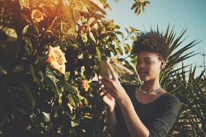 Black girl taking photo of flower